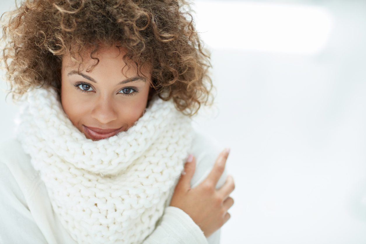 A woman with flawless skin cozies up for the long winter